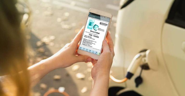 Frau benutzt ein Stromticket auf dem Smartphone um ihr E-Auto zu laden
