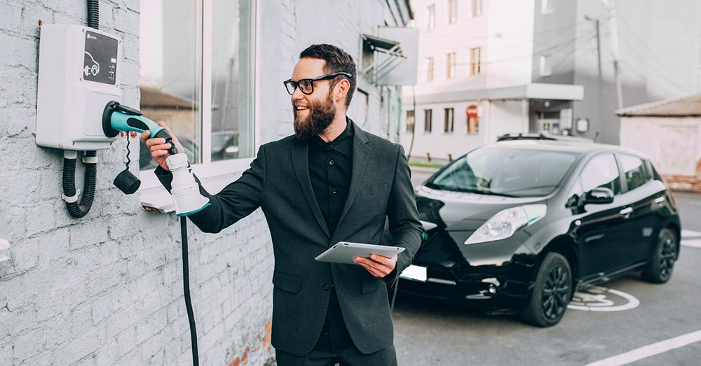Geschäftsmann schließt sein E-Auto an eine Wallbox an